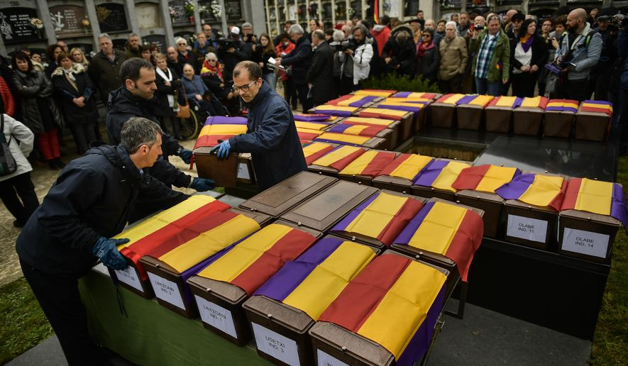People carry the coffins of some of the 46 coffins of unidentified people killed during the Spanish Civil War, at San Jose cemetery, Pamplona, northern Spain, Monday, April 1, 2019. Marking eight decades since the end of the Spanish Civil War, the remains of 46 unidentified victims of the conflict have been reburied in the northern city of Pamplona. More than half a million people died in the 1936-1939 war between rebel nationalist forces led by Gen. Francisco Franco and defenders of the short-lived Spanish republic. (AP Photo/Alvaro Barrientos)