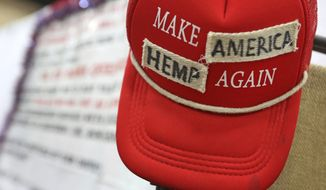 """In this June 14, 2018, photo a """"Make America Great Again"""" hat has been altered and put on display at the Texas Hemp Industries Association booth at the 2018 Texas GOP Convention in San Antonio. Texas this month will remove hemp from its list of controlled substances. The Dallas Morning News reports the Texas Department of State Health Services, as of Friday, will no longer classify hemp as a Schedule I drug, a highly restricted group of substances that includes LSD, heroin and cocaine. (Louis DeLuca/The Dallas Morning News via AP)"""