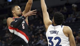 Portland Trail Blazers' Rodney Hood, left, shoots over Minnesota Timberwolves' Karl-Anthony Towns in the first half of an NBA basketball game Monday April 1, 2019, in Minneapolis. (AP Photo/Stacy Bengs)