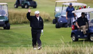 In this July 14, 2018, file photo, President Donald Trump waves to protesters while playing golf at Turnberry golf club, in Turnberry, Scotland. (AP Photo/Peter Morrison) ** FILE **