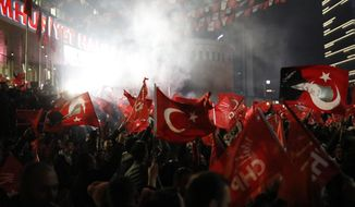 Supporters of the Republican People's Party, CHP, wave Turkish flags, and one with a portrait of Kemal Ataturk, right, as they celebrate after preliminary results of the local elections were announced in Ankara, Turkey, early Monday, April 1, 2019. Erdogan's ruling party has declared victory in the race for mayor of Istanbul, even though the result in Turkey's most populous city and commercial hub is too close to call. State broadcaster TRT says former Prime Minister Binali Yildirim received 48.71 percent of the votes in Sunday's municipal elections while the opposition's candidate, Ekrem Imamoglu, got 48.65 percent. (AP Photo/Burhan Ozbilici)