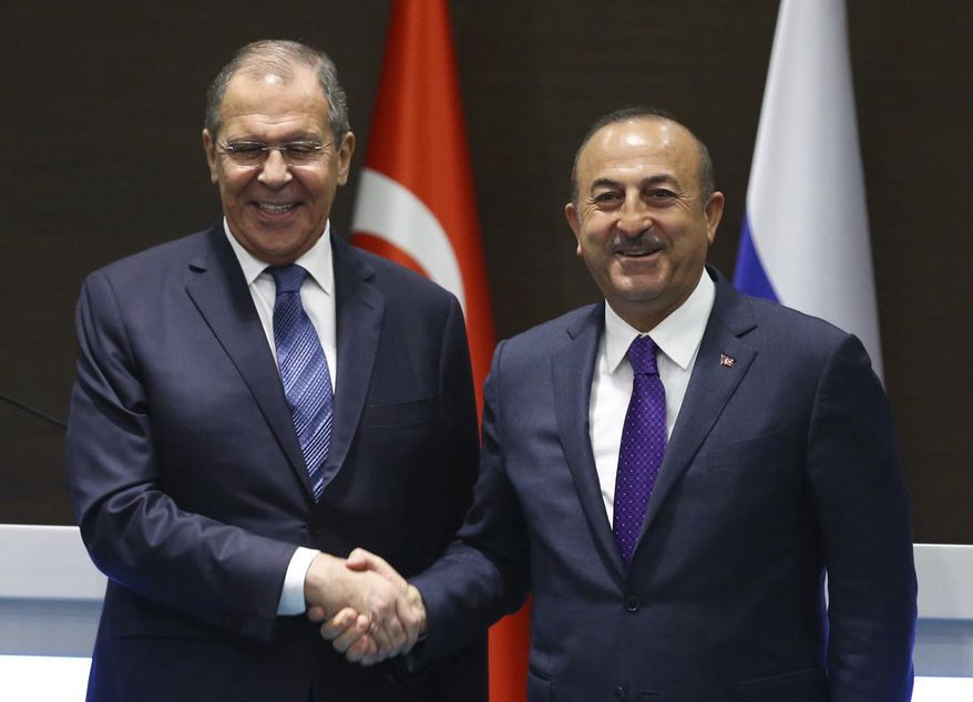 Turkey's Foreign Minister Mevlut Cavusoglu, right, and his Russian counterpart Sergei Lavrov shake hands after a news conference in the Mediterranean coastal city of Antalya, Turkey, Friday, March 29, 2019. Turkey's foreign minister said Friday his country is committed to a deal to purchase advanced Russian surface-to-air missile defense system, despite warnings from Washington that the deal could put the NATO member country's participation in the U.S. F-35 fighter aircraft program at risk. (Turkish Foreign Ministry via AP, Pool)