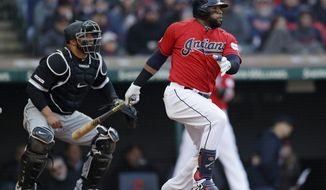 Cleveland Indians' Carlos Santana, right, watches his RBI-single off Chicago White Sox starting pitcher Ivan Nova in the sixth inning of a baseball game, Monday, April 1, 2019, in Cleveland. Jose Ramirez scored on the play. White Sox catcher Welington Castillo, left, also watches the hit. (AP Photo/Tony Dejak)