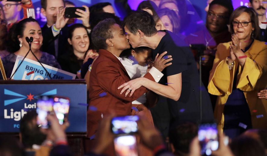 Lori Lightfoot, left, kisses her spouse Amy Eshleman at her election night party Tuesday, April 2, 2019, in Chicago. Lori Lightfoot elected Chicago mayor, making her the first African-American woman to lead the city. (AP Photo/Nam Y. Huh)