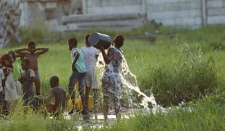 A young girl splashes water on her body at a watering point in Beira, Mozambique, Monday, April, 1, 2019. The death toll from the cyclone has reached over 500, as Mozambican and international health workers raced on Monday to contain the outbreak of cholera in the cyclone-hit city of Beira and surrounding areas, where cases of the disease has jumped to more than 1,000. (AP Photo/Tsvangirayi Mukwazhi)