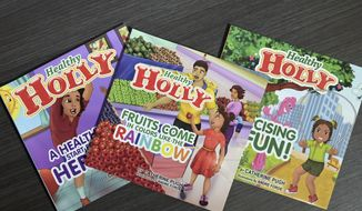 """This March 2019 photo taken in Baltimore, shows copies of then-Baltimore Mayor Catherine Pugh's self-published """"Healthy Holly"""" illustrated paperbacks for children. (Jerry Jackson/The Baltimore Sun via AP) ** FILE **"""