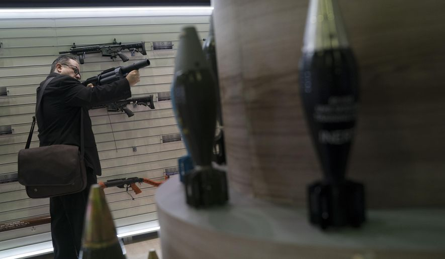 A man tries a multi shot riot gun displayed at the LAAD Defense and Security International Exhibition in Rio de Janeiro, Brazil, Tuesday, April 2, 2019. (AP Photo/Leo Correa)