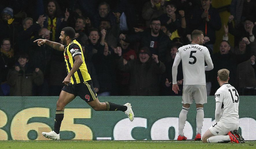 Watford's Troy Deeney, left, celebrates scoring his side's third goal of the game as Fulham's Calum Chambers, second right, and Tim Ream appear dejected during their English Premier League soccer match at Vicarage Road, Watford, England, Tuesday, April 2, 2019. (Nigel French/PA via AP)
