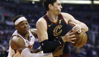 Cleveland Cavaliers forward Cedi Osman, right, has the ball stripped away by Phoenix Suns forward Richaun Holmes, left, during the first half of an NBA basketball game Monday, April 1, 2019, in Phoenix. (AP Photo/Ross D. Franklin)