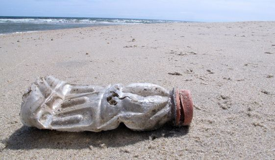 A discarded plastic bottle lies on the beach at Sandy Hook, N.J., on Tuesday, April 2, 2019, the same day as a report released by the environmental group Clean Ocean Action found that volunteers picked up more than 450,000 pieces of litter from New Jersey's coastline last year. (AP Photo/Wayne Parry) ** FILE **
