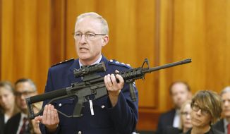 Police acting superintendent Mike McIlraith shows New Zealand lawmakers in Wellington on April 2, 2019, an AR-15 style rifle similar to one of the weapons a gunman used to slaughter 50 people at two mosques. New Zealand lawmakers on Tuesday voted overwhelmingly in favor of new gun control measures during the first stage of a bill they hope to rush into law by the end of next week. (AP Photo/Nick Perry)