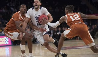 TCU guard Alex Robinson (25) drives to the basket against Texas guard Kerwin Roach II (12) and guard Matt Coleman III during the first half of a semifinal college basketball game in the National Invitational Tournament, Tuesday, April 2, 2019, at Madison Square Garden in New York. (AP Photo/Mary Altaffer)