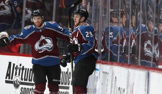 Colorado Avalanche left wing J.T. Compher, left, congratulates center Nathan MacKinnon after he scored a goal against the Edmonton Oilers in the second period of an NHL hockey game Tuesday, April 2, 2019, in Denver. (AP Photo/David Zalubowski)