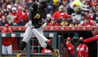 Pittsburgh Pirates first baseman Josh Bell hits an RBI-single off Cincinnati Reds starting pitcher Sonny Gray in the first inning of a baseball game, Sunday, March 31, 2019, in Cincinnati. (AP Photo/John Minchillo)
