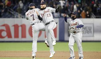 Detroit Tigers shortstop Jordy Mercer (7) and Tigers center fielder Dustin Peterson (13) celebrate by going airborne as Detroit Tigers second baseman Josh Harrison (1) joins them in celebrating after the Tigers defeated the New York Yankees 3-1 in a baseball game, Tuesday, April 2, 2019, in New York. (AP Photo/Kathy Willens)