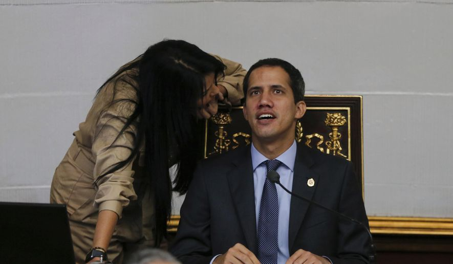 Juan Guaido, right, President of National Assembly and self-proclaimed interim president speaks with lawmaker Delsa Solorzano during a session of the National Assembly in Caracas, Venezuela, Tuesday, April 2, 2019. Venezuela's chief justice on Monday asked lawmakers of the rival pro-government National Constituent Assembly to strip Guaido of his parliamentary immunity, taking a step toward prosecuting him for alleged crimes as he seeks to oust President Nicolas Maduro. (AP Photo/Fernando Llano)