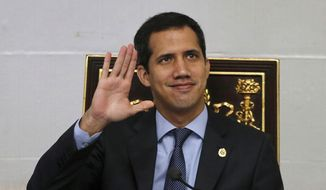 Juan Guaido, president of the National Assembly and self-proclaimed interim president, waves to the gallery during a session of the National Assembly in Caracas, Venezuela, Tuesday, April 2, 2019. Venezuela's chief justice on Monday asked lawmakers of the rival pro-government National Constituent Assembly to strip Guaido of his parliamentary immunity, taking a step toward prosecuting him for alleged crimes as he seeks to oust President Nicolas Maduro. (AP Photo/Fernando Llano)