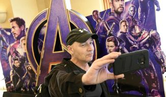"""CinemaCon attendee Luis Saint Amant, of Argentina, takes a selfie in front of an advertisement for the upcoming film """"Avengers: Endgame,"""" on the first day of CinemaCon 2019, the official convention of the National Association of Theatre Owners (NATO) at Caesars Palace, Monday, April 1, 2019, in Las Vegas. (Photo by Chris Pizzello/Invision/AP)"""