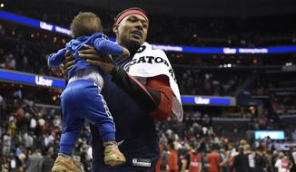 Washington Wizards guard Bradley Beal carries his son Bradley Jr. after an NBA basketball game against the Chicago Bulls, Wednesday, April 3, 2019, in Washington. The Bulls won 115-114. (AP Photo/Nick Wass)