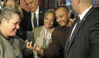Chicago Mayor-elect Lori Lightfoot, center left, poses for a photo as she greets commuters, Wednesday, April 3, 2019, at the Clark/Lake CTA Station in Chicago. Lightfoot, a former federal prosecutor who'd never been elected to public office, defeated Cook County Board President and longtime City Council member Toni Preckwinkle on Tuesday with backing from voters across the city. (Victor Hilitski/Chicago Sun-Times via AP)