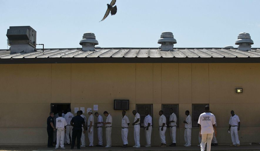 """FILE - In this June 18, 2015, file photo, prisoners stand in a crowded lunch line during a prison tour at Elmore Correctional Facility in Elmore, Ala. The Justice Department has determined that Alabama's prisons are violating the Constitution by failing to protect inmates from violence and sexual abuse and by housing them in unsafe and overcrowded facilities, according to a scathing report Wednesday, April 3, 2019, that described the problems as """"severe"""" and """"systemic."""" (AP Photo/Brynn Anderson, File)"""