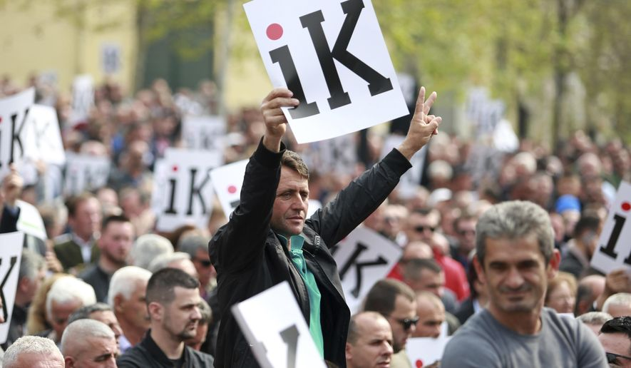 "Albanian opposition supporters hold placards that read ""Go"" in front of the parliament building during a rally in Tirana, Wednesday, April 3, 2019. The opposition accuses the leftist Socialist Party government of Prime Minister Edi Rama of being corrupt and linked to organized crime, which the government denies. (AP Photo/Hektor Pustina)"