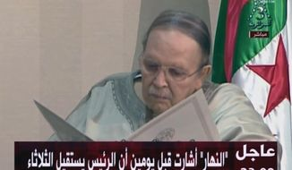 In this image from state TV broadcaster ENTV, Algerian President Abdelaziz Bouteflika, sitting in wheelchair, views the document as he presents his resignation to president of Constitutional Council Tayeb Belaiz, during a meeting Tuesday April 2, 2019.  Algerian President Abdelaziz Bouteflika stepped down on Tuesday after 20 years in office, following six weeks of massive nationwide public protests aimed at pushing him and his much-criticized inner circle from power in the gas-rich nation. (ENTV via AP)