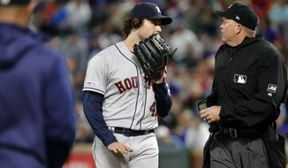 Houston Astros bench coach Joe Espada, left, walks out to intervene in a heated discussion between starting pitcher Gerrit Cole and home plate umpire Ron Kulpa during the seventh inning of the team's baseball game against the Texas Rangers in Arlington, Texas, Wednesday, April 3, 2019. (AP Photo/Tony Gutierrez)