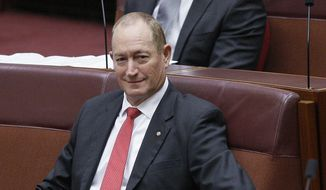 Australian Senator Fraser Anning, center, listens to speeches calling for his censure in Parliament House in Canberra, Australia, Wednesday, April 3, 2019. Anning has been censured by his colleagues for seeking to blame the victims of last month's mosque shootings and vilify Muslims. (AP Photos/Rod McGuirk)