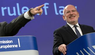 European Commission Vice-President Frans Timmermans, right, listens to questions during a media conference on strengthening the rule of law at EU headquarters in Brussels, Wednesday, April 3, 2019. The European Union is launching action against Poland over allegations that recent justice laws introduced by the government undermine the independence of judges. (AP Photo/Virginia Mayo)