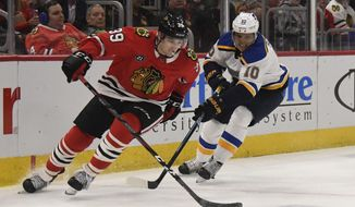 Chicago Blackhawks defenseman Dennis Gilbert (39) is defended by St. Louis Blues center Brayden Schenn (10) during the second period of an NHL hockey game Wednesday, April 3, 2019, in Chicago. (AP Photo/David Banks)