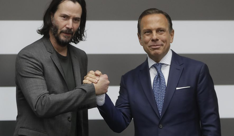 U.S. actor Keanu Reeves, left, shakes hands with Sao Paulo's Governor Joao Doria, in Sao Paulo, Brazil, Wednesday, April 3, 2019. Reeves is in Brazil with producers to choose locations of a science fiction series that should be launched early next year. (AP Photo/Andre Penner)