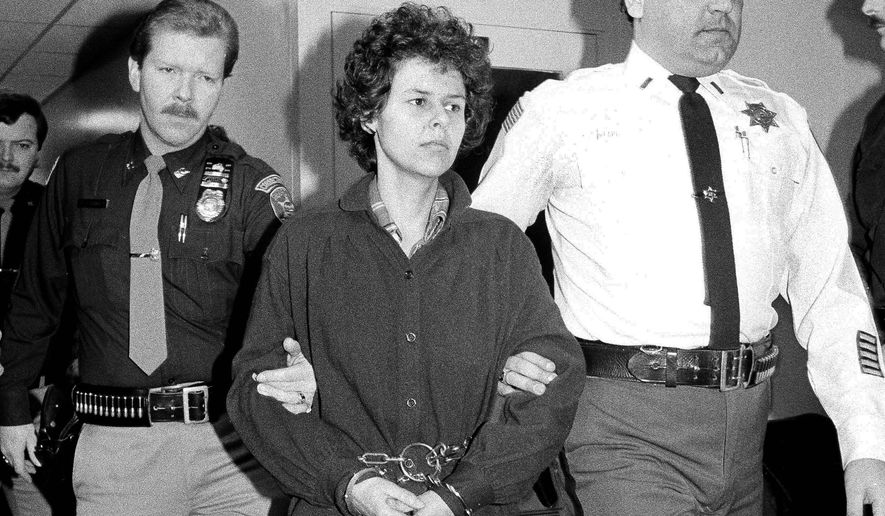 FILE - In this Nov. 24, 1981 file photo, Weather Underground member Judith Clark is handcuffed as she is escorted into Rockland County Courthouse, in New City, N.Y. Supporters of Clark, age 70, a former radical activist who has served more than 36 years of a life sentence for her role in a deadly 1981 Brinks heist, are asking a state panel to grant her parole. (AP Photo/David Handschuh, File)