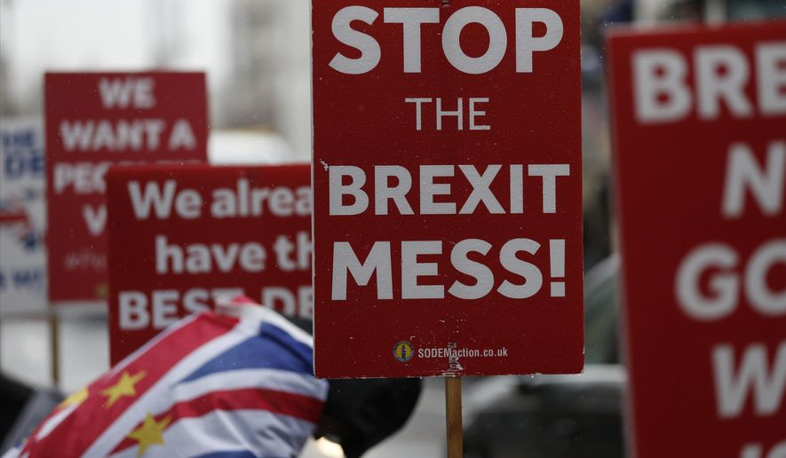 An anti Brexit protester and placards stand in the rain during demonstrations outside the Houses of Parliament in London, Tuesday, April 2, 2019. Britain's Prime Minister Theresa May is set for long Cabinet meeting Tuesday, as the government tries to find a way out of the Brexit crisis, after lawmakers on Monday rejected all alternatives to her European Union withdrawal agreement.(AP Photo/Alastair Grant)