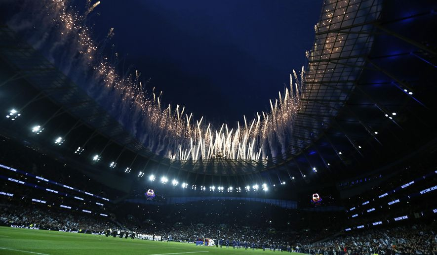 Fireworks explode above the stadium as the teams stand on the pitch before the start of the English Premier League soccer match between Tottenham Hotspur and Crystal Palace, the first Premiership match at the new Tottenham Hotspur stadium in London, Wednesday, April 3, 2019. (AP Photo/Kirsty Wigglesworth)