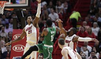 Boston Celtics guard Kyrie Irving (11) loses the ball as Miami Heat center Hassan Whiteside (21) and guard Dwyane Wade (3) defend during the first half of an NBA basketball game Wednesday, April 3, 2019, in Miami. (AP Photo/Lynne Sladky)