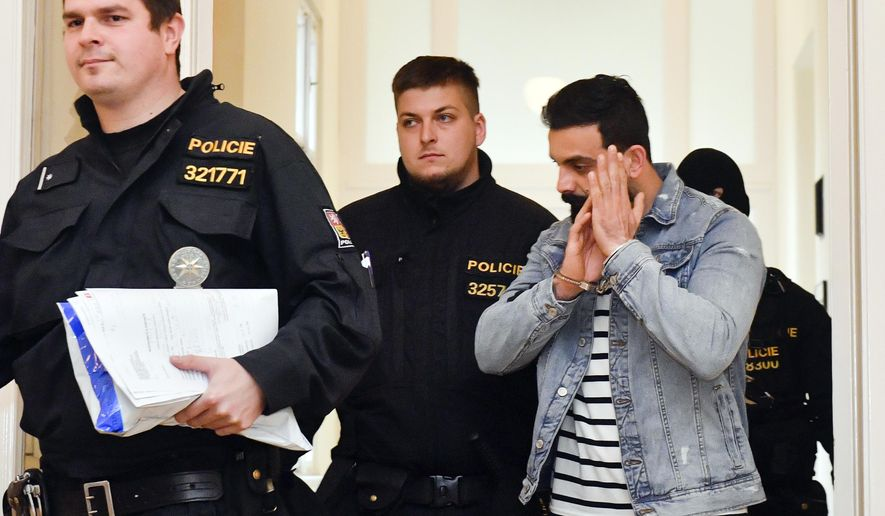 Iraqi Ammar Raheem Mahmod Mahmod, right, suspected of terrorism is escorted at the Municipal Court in Prague, Friday, March 29, 2019. The court ruled that Iraqi terror suspects Amar Rahim Mahmoud Mahmoud and Riyam Shukri Sali Badri, who were arrested at Prague airport on Wednesday, be remanded in custody, and both agreed with the extradition to Austria, Prague Municipal State Attorney's Office spokesman said today. (Vit Simanek/CTK via AP)
