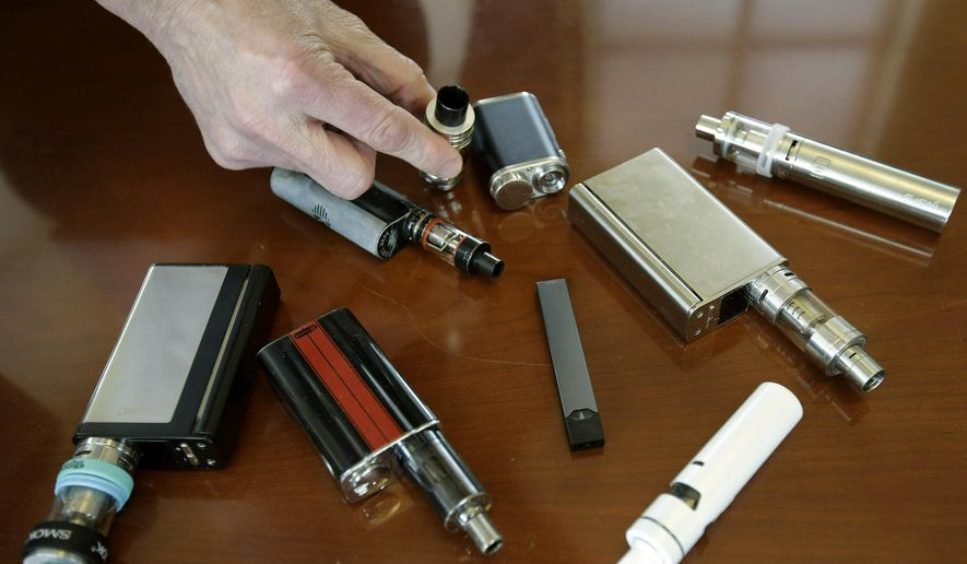 In this April 10, 2018, file photo, a high school principal displays vaping devices that were confiscated from students in such places as restrooms or hallways at the school in Massachusetts. On Wednesday, April 3, 2019, the U.S. Food and Drug Administration said it has not established a direct connection between vaping and seizures but is seeking more information. Regulators noted that seizures and convulsions are a known side effect of nicotine poisoning. (AP Photo/Steven Senne, File) **FILE**