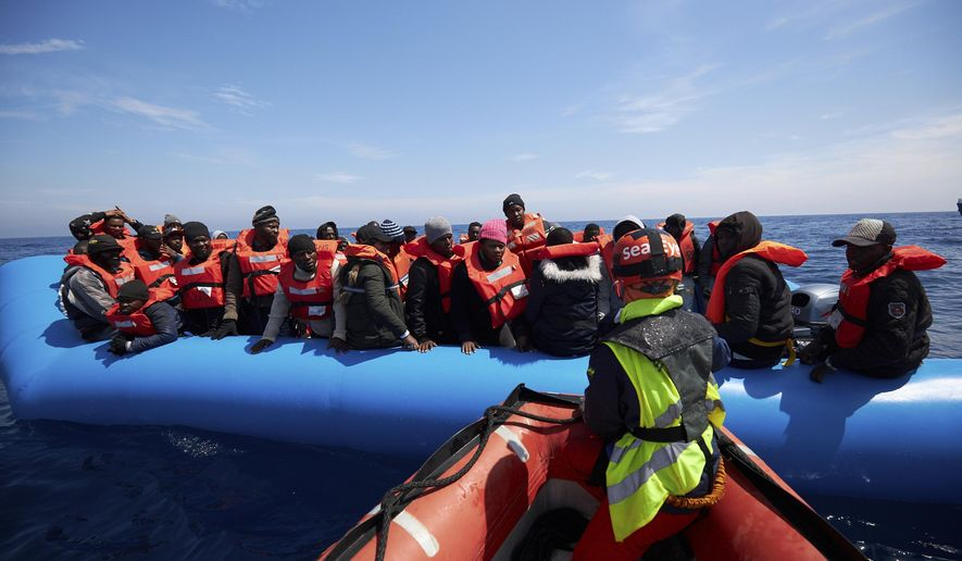 Migrants on a rubber dinghy are approached by Sea-Watch rescue ship's staffers in the waters off Libya Wednesday, April 3, 2019. The German humanitarian group Sea-Watch says the ship it operates in the central Mediterranean Sea has rescued 64 migrants in waters off Libya. Sea-Watch wrote Wednesday on Twitter that the people brought to safety from a rubber dinghy included 10 women, five children and a newborn baby. The group said it carried out the rescue off the coast of Zuwarah after Libyan authorities couldn't be reached. Sea-Watch is asking Italy or Malta to open a port to the rescue ship, the Alan Kurdi. (Fabian Heinz/Sea-eye.org via AP)