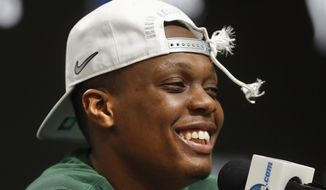 FILE - In this March 31, 2019, file photo, Michigan State guard Cassius Winston (5) smiles while answering questions during a news conference after beating Duke 68-67 in an NCAA men's East Regional final college basketball game, in Washington. Winston has joined a select group of players in program history as an All-America player and Big Ten player of the year. If he can help the Spartans win two more games, he'll join Magic Johnson and Mateen Cleaves as the school's national championship-winning point guards. (AP Photo/ Mark Tenally, File) **FILE**