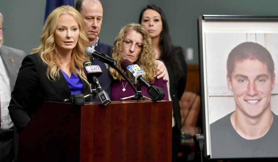 FILE - In this May 5, 2017 file photo, Jim and Evelyn Piazza stand by as Centre County District Attorney Stacy Parks Miller, left, announces the results of an investigation into the death of their son Timothy Piazza, seen in photo at right, a Penn State University fraternity pledge, during a press conference in Bellefonte, Pa.   Three ex-Penn State fraternity brothers have been sentenced to jail on hazing charges in connection to the February 2017 death of Piazza.  Sentences handed down Tuesday, April 2, 2019,  to the three former Beta Theta Pi members range from 30 days to three months in jail.  (Abby Drey/Centre Daily Times via AP, File)