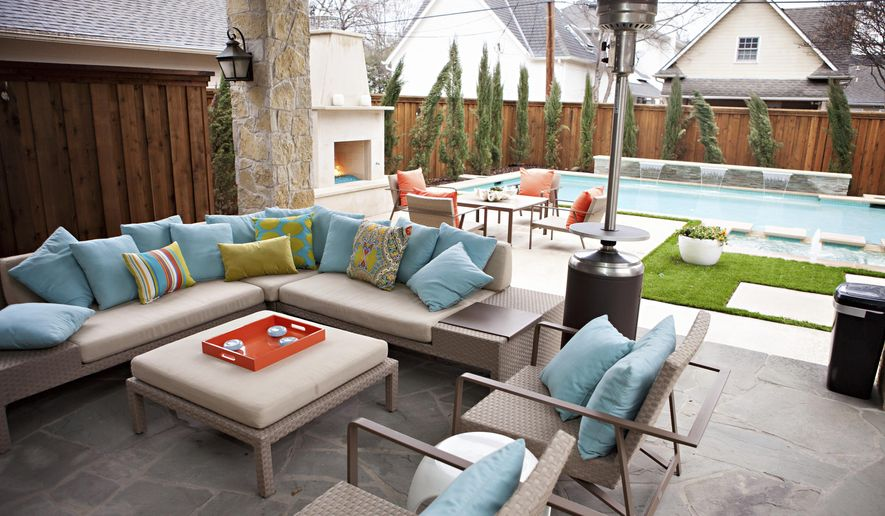 This undated photo shows an outdoor space at a home in Texas designed by Abbe Fenimore, founder of Studio Ten 25. With the addition of an outdoor fireplace and a standing space heater, a backyard can be focused on the swimming pool during the summer but be enjoyed even in cooler weather. (Melanie Johnson Photography/Abbe Fenimore via AP)