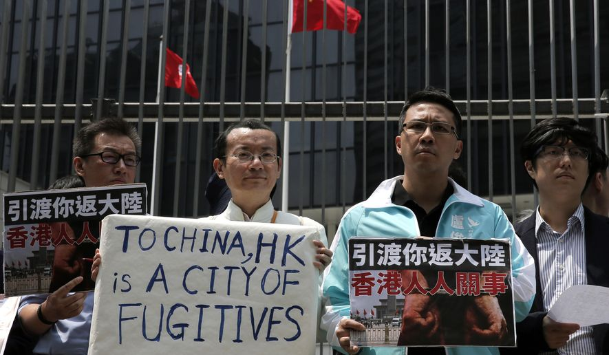 Protesters raise placards against Hong Kong's extradition law at the Legislative Council Hong Kong, Wednesday, April 3, 2019. First and second readings of the proposed changes to Hong Kong's extradition law take place at Legislative Council of Hong Kong. Business and human rights groups are expressing concern over the proposed changes that would regularize the extradition of suspects to mainland China where they say they could be subject to torture and unfair prosecution. (AP Photo/Vincent Yu)