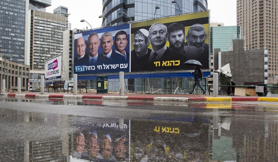 """In this Saturday, March 16, 2019, file photo, an Ultra-Orthodox Jewish man looks at an elections billboards of the Blue and White party leaders, from left to right, Moshe Yaalon, Benny Gantz, Yair Lapid and Gabi Ashkenazi, alongside a panel on the right showing Prime Minister Benjamin Netanyahu flanked by extreme right politicians, from the left, Itamar Ben Gvir, Bezalel Smotrich and Michael Ben Ari in Ramat Gan, Israel, In a charged campaign that has been heavy on insults and short on substance, Israel's conflict with the Palestinians has been notably absent from the discourse. Hebrew reads on the left billboard """"The nation of Israel lives"""" and on the right billboard """"Kahana Lives"""" in a reference to a banned ultranationalist party. (AP Photo/Oded Balilty, File)"""