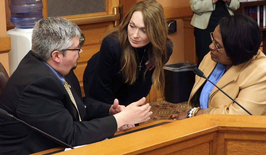 Kansas state Reps. Kyle Hoffman, left, R-Coldwater; Kristey Williams, center, R-Augusta, and Valdenia Winn, D-Kansas City, confer during negotiations with the Senate on school funding and education policy issues, Wednesday, April 3, 2019, at the Statehouse in Topeka, Kansas. House Republicans have given up on pushing for an alternative to Democratic Gov. Laura Kelly's proposal to boost education funding by at least $90 million a year. (AP Photo/John Hanna)