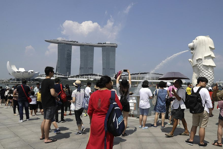 FILE - In this June 7, 2018, file photo, tourists photograph the Merlion, right, one of the icons of Singapore, with the Marina Bay Sands in the background. On Wednesday, April 3, 2019, casino company Las Vegas Sands announced it'll spend $3.3 billion to expand its property in Singapore by adding an entertainment arena, another hotel tower and additional convention space. (AP Photo/Wong Maye-E, File)