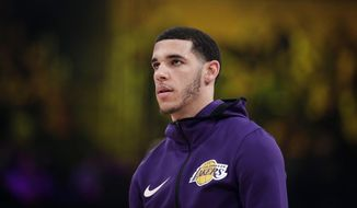 """In this Dec. 21, 2018 photo, Los Angeles Lakers' Lonzo Ball warms up before an NBA basketball game against the New Orleans Pelicans in Los Angeles. Lonzo Ball and his company Big Baller Brand are suing co-founder Alan Foster, alleging he conspired to steal millions of dollars from the shoe and clothing line. The lawsuit filed Tuesday, April 2, 2019, in Los Angeles Superior Court says Foster concocted """"a fraudulent scheme"""" to enrich himself with company money and also use it to buy property in Ethiopia. (AP Photo/Jae C. Hong)"""