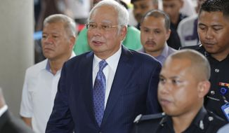 Former Malaysian Prime Minister Najib Razak, center, walks into a courtroom at Kuala Lumpur High Court in Kuala Lumpur, Malaysia, Wednesday, April 3, 2019. Najib appeared in court Wednesday for the start of his corruption trial, exactly 10 years after he was first elected to office only to suffer a spectacular defeat last year on allegations he pilfered millions of dollars from a state investment fund. (AP Photo/Vincent Thian)