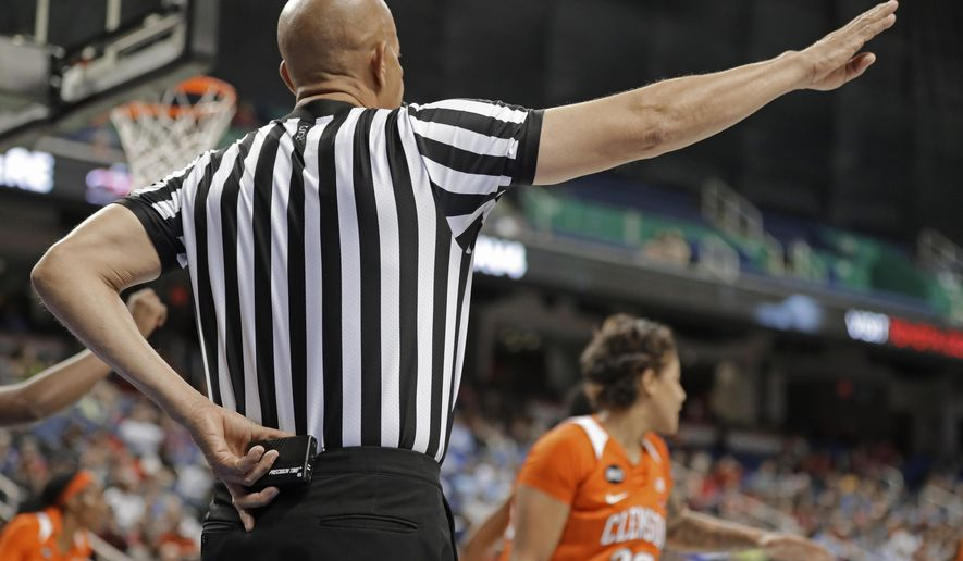 In this photo taken March 8, 2019, a referee prepares to start a play using a Precision Time device during the first half of an Atlantic Coast Conference women's tournament basketball game in Greensboro, N.C. The Precision Time system created more than two decades ago by former referee Mike Costabile currently is used at nearly every level of the sport, including the NBA and college basketball's NCAA Tournament. Costabile estimates the ability to stop the clock automatically on a referee's whistle can save roughly 90 seconds formerly lost to reaction time when timekeepers manually stopped the clock. (AP Photo/Chuck Burton)