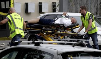 FILE - In this March 15, 2019, file photo, ambulance staff take a man from outside a mosque in central Christchurch, New Zealand. The man authorities believe carried out the Christchurch mosque attacks is due to make his second court appearance via video link on Friday, April 4, 2019, although media photographs won't be allowed and reporting on the proceedings will be limited by New Zealand law. Fifty people died in the March 15 attacks on two mosques. (AP Photo/Mark Baker, File)